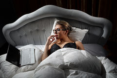 Woman lying on bed with a laptop Royalty Free Stock Photo