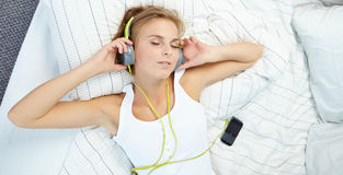Woman lying on bed while listening music through headphone Stock Photos