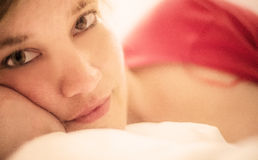 Woman lying in bed Stock Images