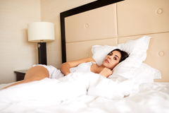 Woman lying in bed looking at camera Royalty Free Stock Image