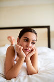 Woman lying in bed looking downcast. Stock Photo