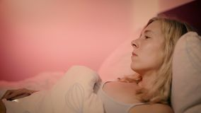 Woman lying in bed looking at smartphone feeling upset and putting the phone down while sighing stock video footage