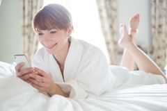 Woman lying on a bed with mobile phone Stock Images