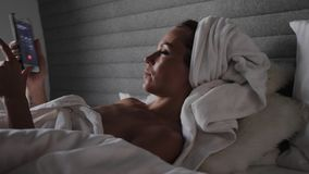 Woman lying on a bed with mobile phone stock footage
