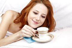 Woman lying in the bed near cup of coffee. Royalty Free Stock Photography