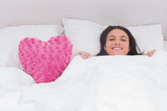 Woman lying in bed next to a fluffy heart pillow Stock Photography