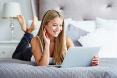 Woman lying on the bed with notebook Stock Photography