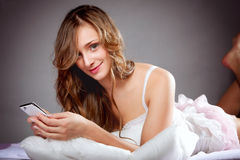 Woman lying on bed with phone Royalty Free Stock Image