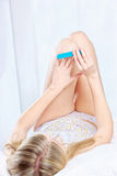 Woman lying in bed and polishing nails Stock Photography