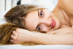 Woman lying in bed. Positive young woman lying in bed with opened eyes and smiling royalty free stock images