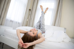 Woman lying on the bed with raised legs up Stock Photos