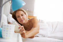 Woman Lying In Bed Reaching To Check Mobile Phone Royalty Free Stock Image