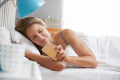 Woman Lying In Bed Reaching To Check Mobile Phone Royalty Free Stock Photo
