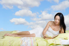 Woman lying in bed and reading the book Royalty Free Stock Photography