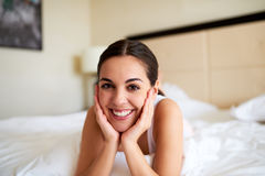 Woman lying in bed resting chin in hands. Royalty Free Stock Photo