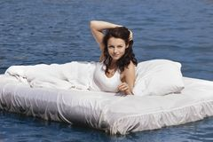 Woman lying on the bed in the sea Royalty Free Stock Photo