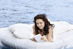 Woman lying on the bed in the sea Stock Photos