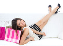 Woman lying on a bed with shopping bags Royalty Free Stock Photos