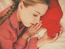 Woman sleeping with warm red hot water bottle Royalty Free Stock Photos