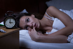 Woman lying in bed sleepless. At night Stock Photos
