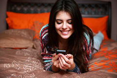 Woman lying on the bed with smartphone Royalty Free Stock Photography
