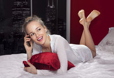 Woman lying on bed with smartphone l Stock Image