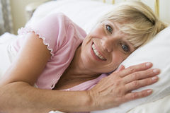 Woman lying in bed smiling Royalty Free Stock Photography