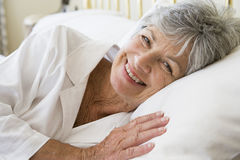 Woman lying in bed smiling Royalty Free Stock Photos
