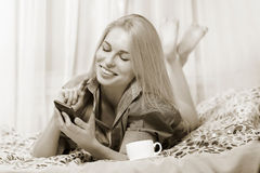 Woman lying at the bed and smiling. Stock Images
