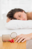 Woman lying in bed by spilt bottle of pills on table Royalty Free Stock Photography