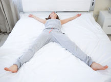 Woman lying on the bed in star pose Royalty Free Stock Photography