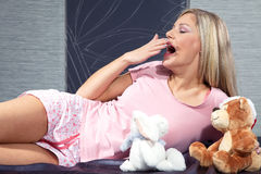 Woman lying in bed with stuffed animal Royalty Free Stock Photography