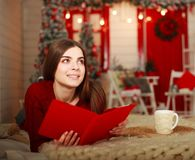 Woman lying on bed with tablet on background of Christmas Stock Photography