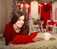 Woman lying on bed with tablet on background of Christmas Stock Photo
