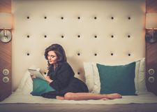 Woman lying on a bed with tablet pc Royalty Free Stock Photography