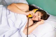 Woman lying on bed talking on landline phone Royalty Free Stock Photos