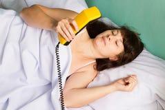 Woman lying on bed talking on landline phone Stock Photos