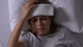 Woman lying in bed with towel on forehead, taking pills, cold treatment, illness. Stock footage stock footage