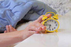 Woman lying in bed turning off an alarm clock close up. Hate waking up early. Selective focus on clock Royalty Free Stock Photo