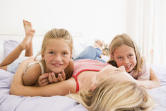 Woman lying in bed with two young girls smiling Stock Photos