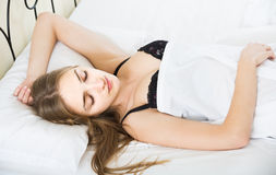 Woman lying in bed under sheet with closed eyes Royalty Free Stock Image