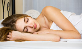 Woman lying in bed under sheet with closed eyes Stock Photos
