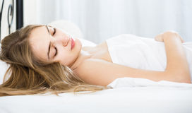 Woman lying in bed under sheet with closed eyes Royalty Free Stock Photography