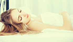 Woman lying in bed under sheet with closed eyes. Young american woman lying in bed under sheet with closed eyes Stock Photo