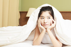 Woman lying in bed underneath the quilt and smiling Stock Image