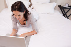 Woman lying on the bed using her laptop Royalty Free Stock Photo