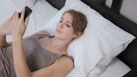 Woman Lying in Bed Using Internet on Smartphone. 4k , high quality stock video footage