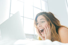 Woman lying on the bed and using laptop computer Stock Photo