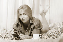 Woman lying at the bed and using mobile phone and taking offence. Sepia toned Royalty Free Stock Photography