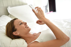 Woman lying in bed using smartphone. Woman laying on bed and using smartphone Stock Photography